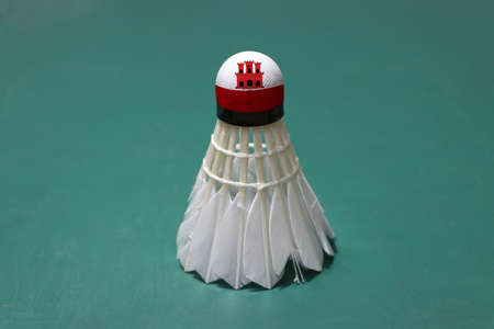 Used shuttlecock and on head painted with Gibraltar flag put vertical on green floor of Badminton court. Badminton sport concept.