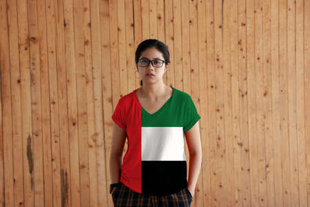 Woman wearing United Arab Emirates flag color shirt and standing with two hands in pant pockets on the wooden wall background, green white and black with a vertical one fourth width red bar at the hoist.