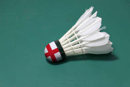 Used shuttlecock and on head painted with England flag put horizontal on green floor of Badminton court. Badminton sport concept. Stock Photo