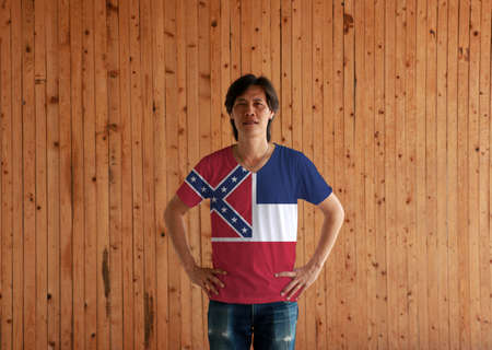 Man wearing Mississippi flag color shirt and standing with akimbo on the wooden wall background, the states of America.