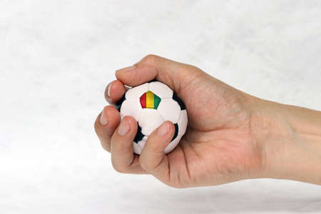 Mini football in hand and one black point of football is Guinea flag on white background. Concept of sport or the game in handle.