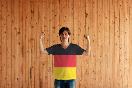 Man wearing Germany flag color of shirt and standing with raised both fist on the wooden wall background, black red and yellow color.