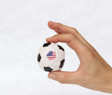 Mini ball of football in hand and one black point of football is United States of America flag, hold it with two finger on white background. Concept of sport or the game in handle or minor matter.