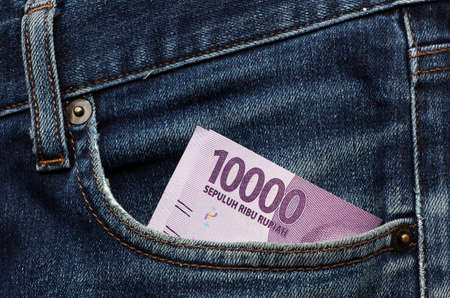 Banknote money ten thousand Indonesia Rupiah in the pocket of blue jeans. Concept of saving money or finance. 스톡 콘텐츠