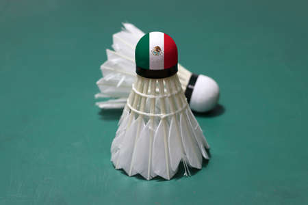 Used shuttlecock and on head painted with Mexico flag put vertical and out focus shuttlecock put horizontal on green floor of Badminton court. Badminton sport concept. Stock Photo