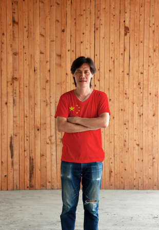 Man wearing China flag color shirt and cross one's arm on wooden wall background, large golden star within an arc of four smaller golden stars on red.