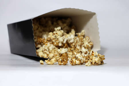 Heap of chocolate and caramel popcorn from paper box on the white floor. It is the corn of a variety with hard kernels that swell up and burst open with a pop when heated. Banque d'images