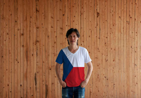 Man wearing Czech Republic flag color shirt and standing with two hands in pant pockets on the wooden wall background, two equal horizontal of white and red with a blue triangle on the hoist side.