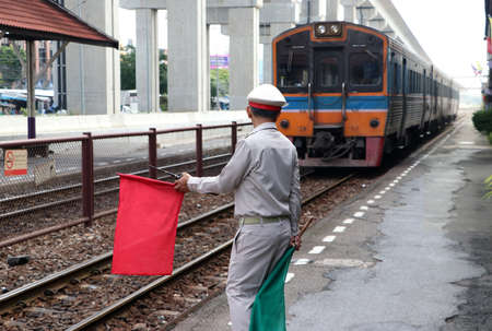 Train officer is acting to signal safety precautions for passengers and people while the train is landing at the platform, red flag means danger or be extra careful and green flag means safe.