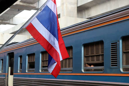 Thai flag at train station and background the train is run leaving the station. Stockfoto