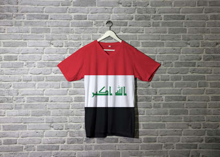"Iraq flag on shirt and hanging on the wall with brick pattern wallpaper, red white and black with ""God is greatest"""