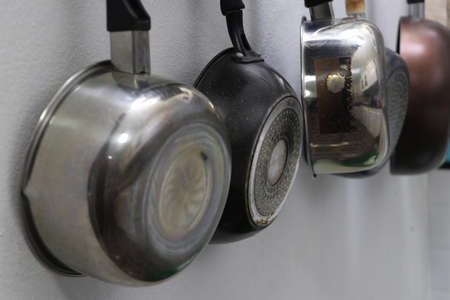 Metal pans and pots for cooking, hanging in the kitchen. Foto de archivo - 128036053
