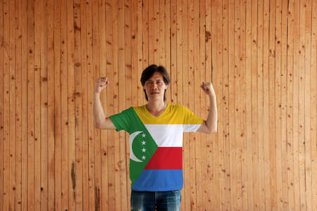 Man wearing Comoros flag color of shirt and standing with raised both fist on the wooden wall background, yellow white red and blue with  green chevron, crescent and star.