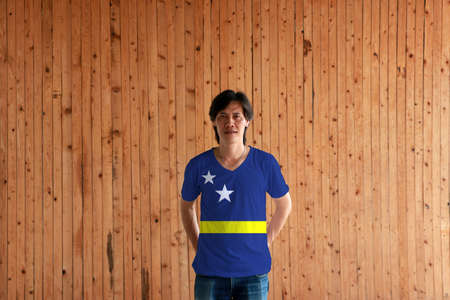 Man wearing Curacao flag color of shirt and standing with crossed behind the back hands on the wooden wall background, blue field with a horizontal yellow stripe slightly below the midline and two white stars. Banco de Imagens