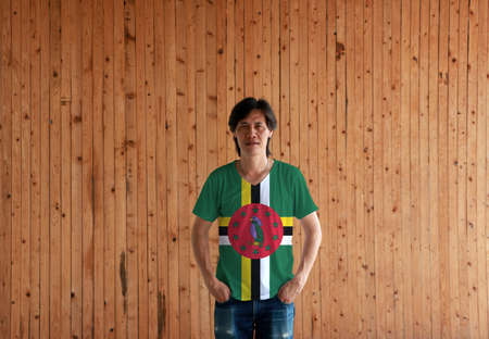 Man wearing Dominica flag color shirt and standing with two hands in pant pockets on the wooden wall background, green field with cross of yellow black and white, Sisserou Parrot and star.