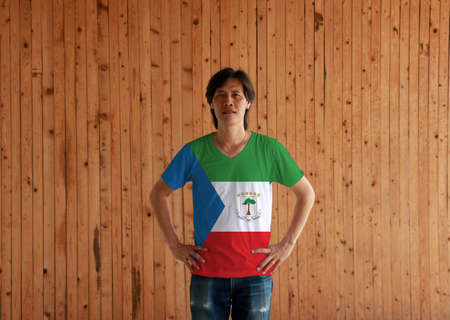 Man wearing Equatorial Guinea flag color shirt and standing with akimbo on the wooden wall background, green white and red with a blue triangle and the National Coat of arms.