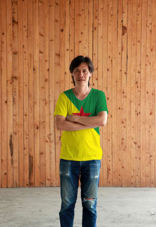 Man wearing French Guiana flag color shirt and cross ones arm on wooden wall background, green and yellow with red star.