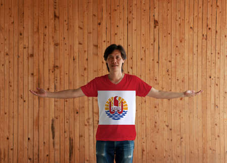 Man wearing French Polynesia flag color shirt and standing with arms wide open on the wooden wall background, red and white; centered is a disk with Polynesian canoe rides on the wave.