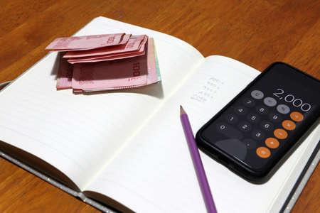 Writing the amount of money in the book by pencil with calculator and a certain amount of Thai baht. Concept of financial.