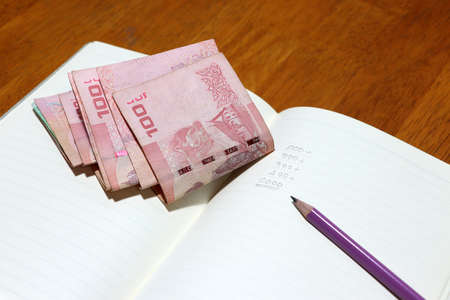 Writing the amount of money in the book by pencil with a certain amount of Thai baht. Concept of financial.