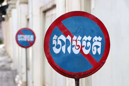 Traffic Signs on the road beside the wall, no-parking sign in Cambodian language.