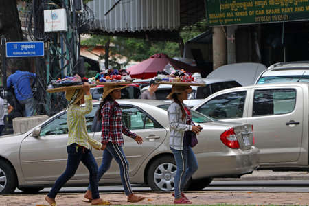 Phnom Penh, Cambodia, August 17, 2019 :  Cambodian females street vendor put the threshing basket of cosmetics and accessories for women on her head and walking for sell.