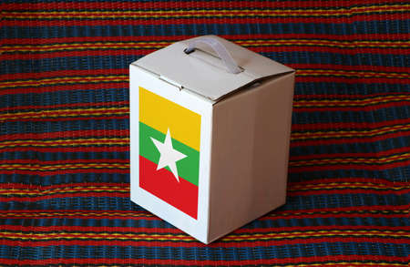 Myanmese flag on white box with stripe background, Paper packaging for put products. The concept of export trading from Myanmar.