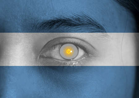 Human face painted with Argentina flag and Sun of May on the center of eye or eyeball. Human eye painted with flag of Argentina.
