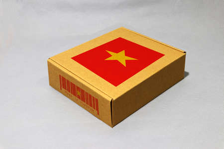 Vietnam flag on brown box with barcode and the color of nation flag, paper packaging for put products. The concept of export trading from Vietnam. Stock Photo