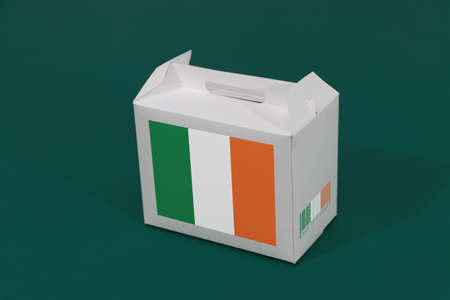 Ireland flag on white box with barcode and the color of nation flag on green background. The concept of export trading from Ireland, paper packaging for put products.