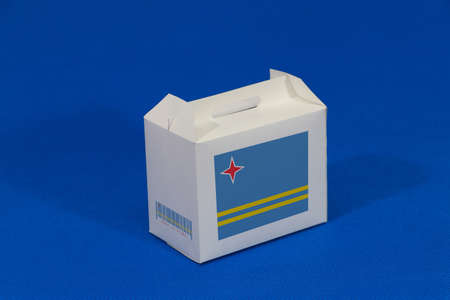 Aruba flag on white box with barcode and the color of nation flag on blue background. The concept of export trading from Aruba, paper packaging for put products. Standard-Bild