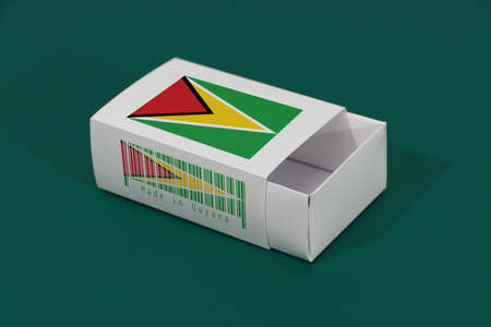 Guyana flag on white box with barcode and the color of nation flag on green background, paper packaging for put match or products. The concept of export trading from Guyana.