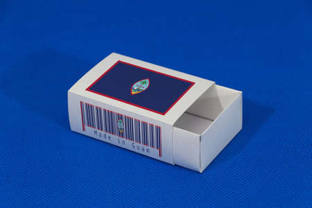 Guam flag on white box with barcode and the color of nation flag on blue background, paper packaging for put match or products. The concept of export trading from Guam. Stock Photo