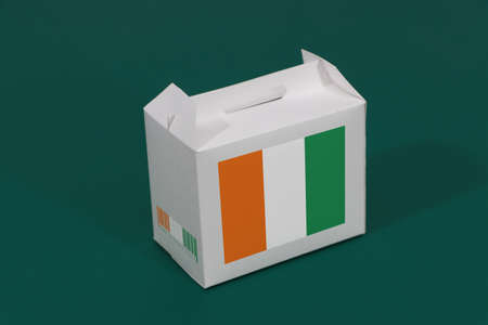 Ivory Coast flag on white box with barcode and the color of nation flag on green background. The concept of export trading from Ivory Coast, paper packaging for put products.
