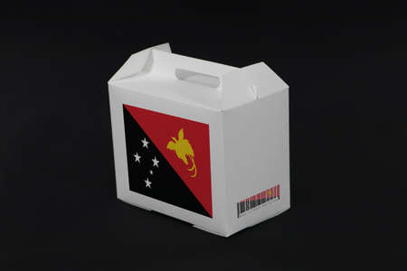 Papua New Guinea flag on white box with barcode and the color of nation flag on black background. The concept of export trading from Papua New Guinea, paper packaging for put products.