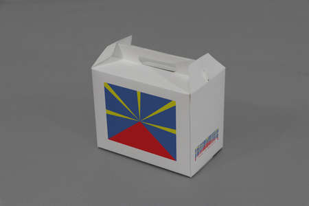 Reunion flag on white box with barcode and the color of nation flag on grey background. The concept of export trading from Reunion, paper packaging for put products.