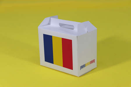 Romanian flag on white box with barcode and the color of nation flag on yellow background. The concept of export trading from Romania, paper packaging for put products.