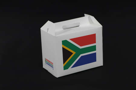 South Africa flag on white box with barcode and the color of nation flag on black background. The concept of export trading from South Africa, paper packaging for put products. Standard-Bild