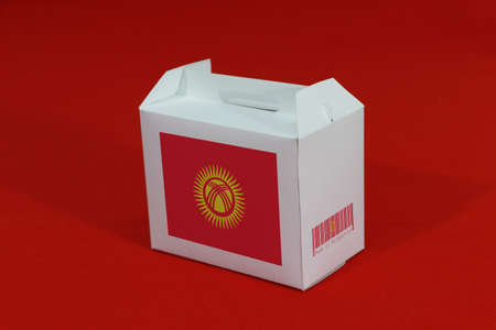 Kyrgyzstan flag on white box with barcode and the color of nation flag on red background. The concept of export trading from Kyrgyzstan, paper packaging for put products. Standard-Bild