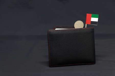 One coin of United Arab Emirates one dirham money and mini UAE flag stick on the black wallet with dark background. Concept of finance or currency.