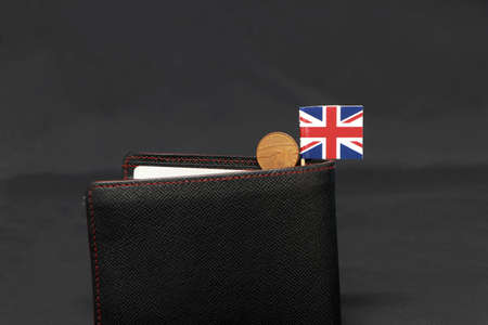 One Penny British decimal coin money and mini Union Jack flag stick on the black wallet with dark background. Concept of finance or currency.