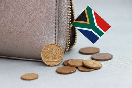 Heap of South African Rand coin money and mini South African flag stick on the leather wallet on grey background. Concept of finance or currency.