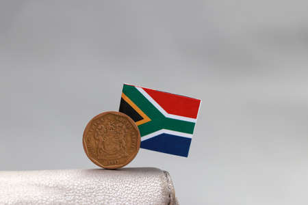 One coin of South African Rand money and mini South African flag stick on the leather wallet on grey background. Concept of finance or currency.