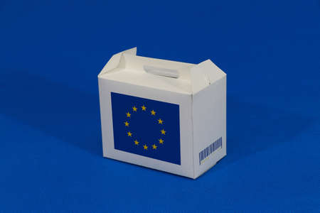 European Union flag on white box with barcode and the color of flag on blue background. The concept of export trading from Europe, paper packaging for put products.