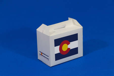 Colorado flag on white box with barcode and the color of state flag on blue background. The concept of export trading from Colorado, paper packaging for put products.