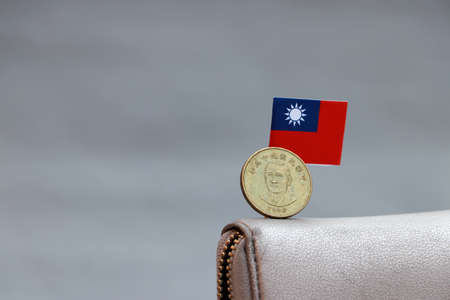 One coin of Taiwan fifty dollars money on obverse, portrait of Dr.Sun Yat-Sen, first president and mini Taiwan flag stick on the leather wallet on grey background. Concept of finance or currency.