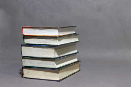 Stack of the books collection on grey background. Reading or education concept.