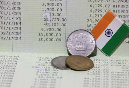Three coins of Rupee Indian money with mini India flag on the book bank. Concept of Saving money or finance.