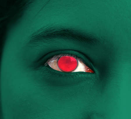 Human face painted Bangladesh flag with a red disc on the center of eye or eyeball. Human eye painted with flag of Bangladesh. Фото со стока
