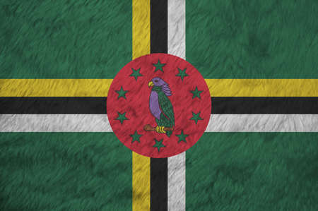 Towel fabric pattern flag of Dominica, Crease of Domincian flag background. A green field with cross of yellow black and white, Sisserou Parrot on red disk and star